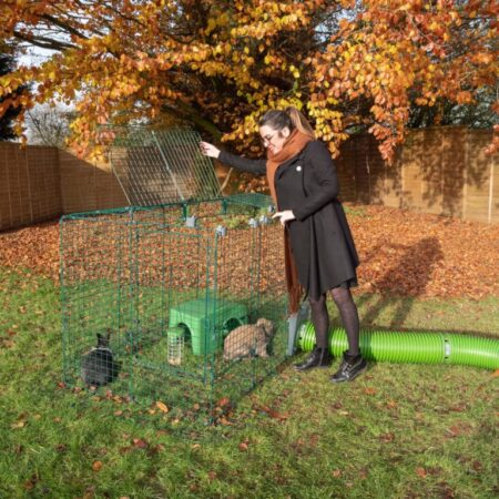 En kvinna utomhus på hösten och två kaniner i en kaningård